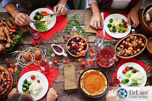An image of four people with plates eating at a holiday table