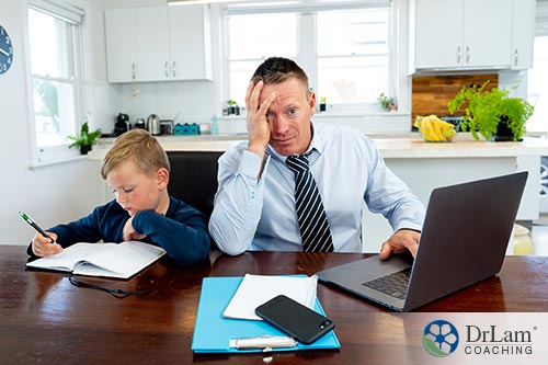 An image of a stressed out father trying to work while his son sits next to him doing schoolwork