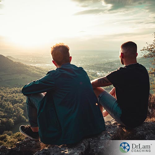 An image of a young man with his father watching the sun set in a valley