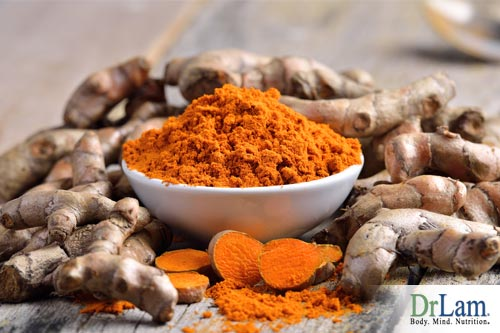 A pile of turmeric root and a bowl of powdered turmeric sitting on top. Turmeric health benefits can soothe rampant inflammation.