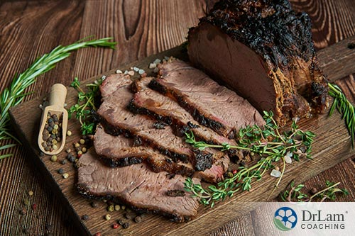An image of a well done roast sliced on a wood cutting board with herbs around it