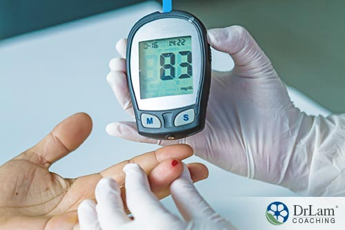 An image of a nurse checking a patient's blood sugar level with a glucose monitor