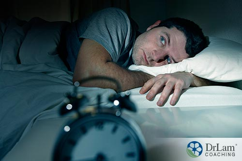 An image of a man laying in bed unable to sleep
