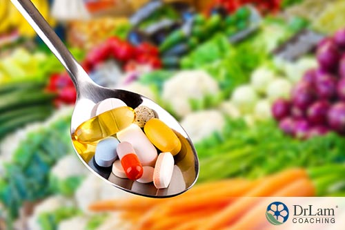 An image of supplements in a spoon with various vegetables in the background