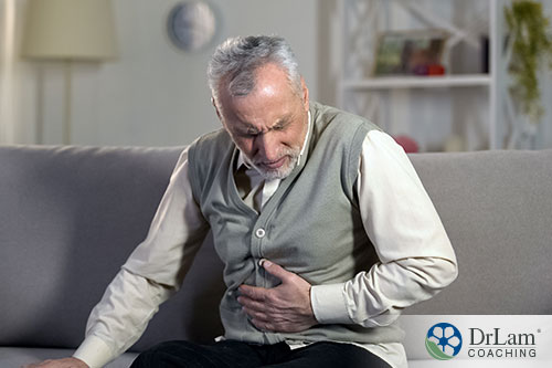 An image of an older man holding his abdomen in discomfort while sitting on the couch