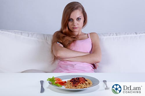 An image of a woman sitting with her arms crossed while she looks at a plate of untouched food