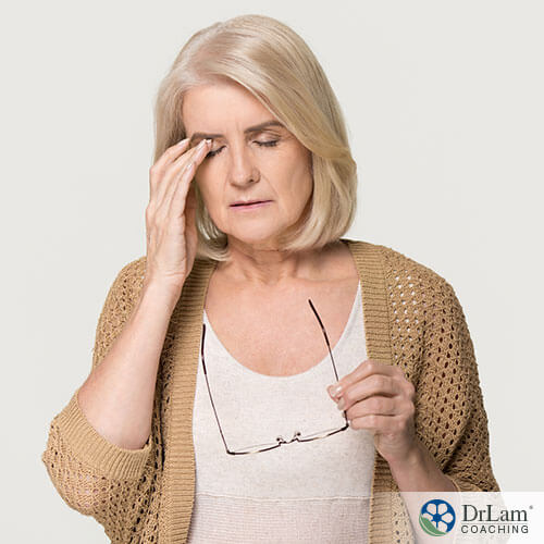 An image of an older woman rubbing her eyes and holding her glasses