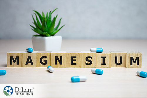 An image of wood blocks spelling out magnesium with blue and white capsules around it