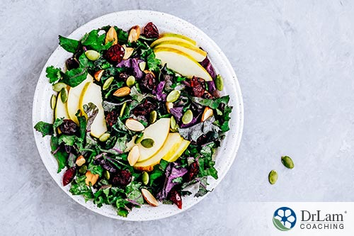 An image of a kale salad with seeds, nuts and apple slices