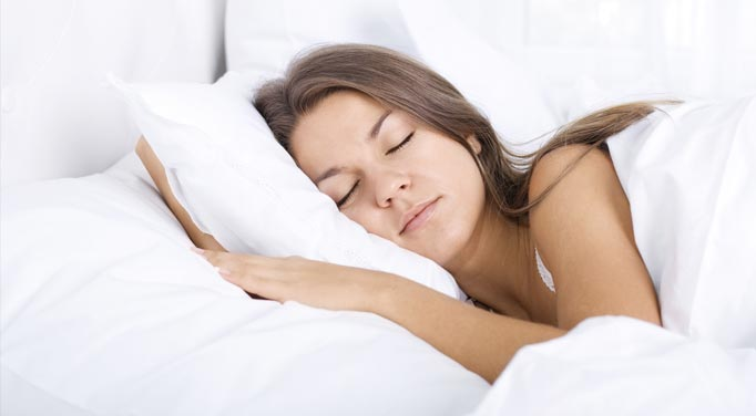 A young woman sleeping peacefully, which the best temperature for sleeping assist with