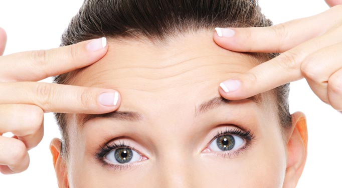 A young woman with fingers to her forehead indicating wrinkles, getting rid of these outweighs D-Ribose Side Effects