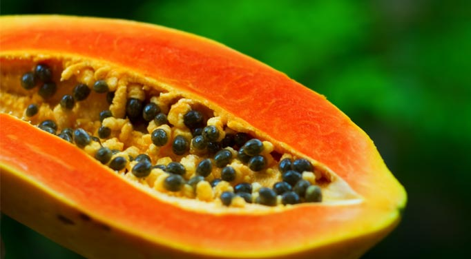 A cut papaya. Papayas contain papain, an enzyme commonly found in digestive enzyme supplements that aid in digestion.