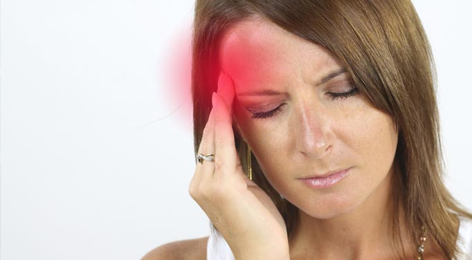 A woman with a headache who could do with folic acid benefits