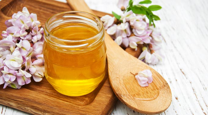 A jar and spoonful of honey, one of the most well known healthy sweeteners