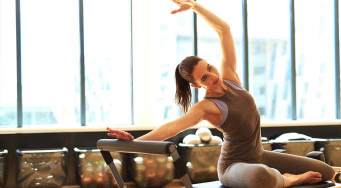 Woman performing stretches with an exercise machine. Keeping the body active and the metabolism stable is critical to improving liver health and the body.