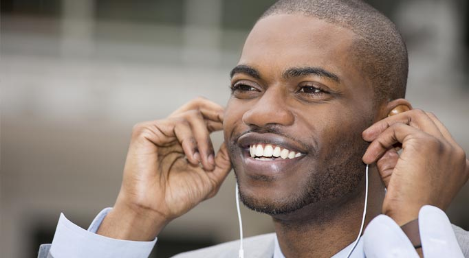 A young man smiles as he puts earphones in, showing how music and the brain interact to improve mood