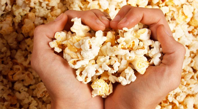 Two hands cupping popcorn in a heart shape, representing the health benefits of this low calorie snack