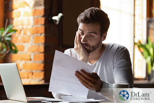 An image of a stressed man looking at a paper