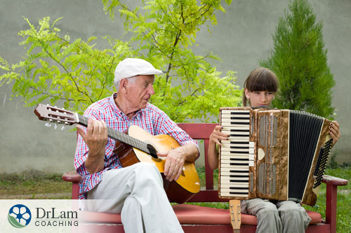 An image of a older man and young lady playing musical instruments together