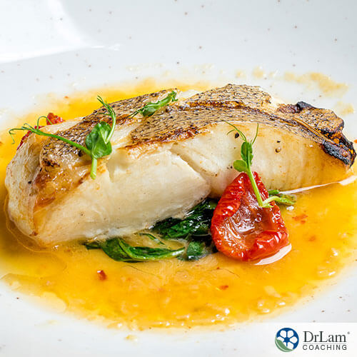 An image of cooked cod with greens and a tomato