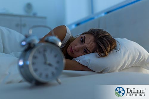 An image showing woman in bed watching the clock