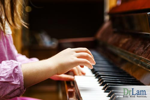 A closeup of a child's hands as she plays the piano, representing the benefits of music and the brain in creating mental pathways