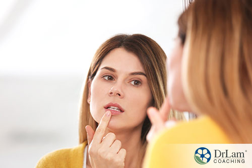 an image of a young woman looking at her lip in the mirror