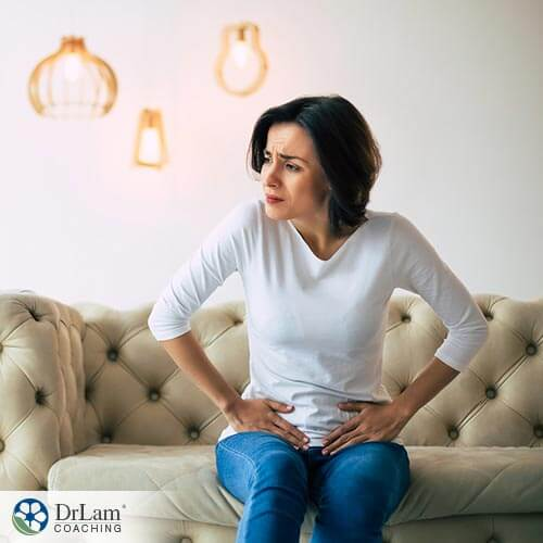 An image of a woman in pain holding her pelvic area