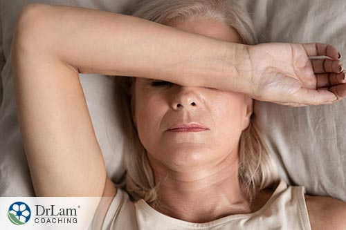 An image of a fatigued woman laying with one arm over her face