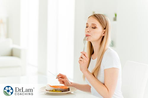 An image of a woman eating a bite of baked salmon