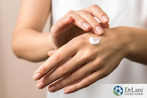 An image of a woman rubbing cream on her hand