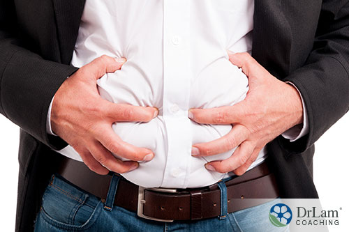 An image of a man holding his bloated stomach