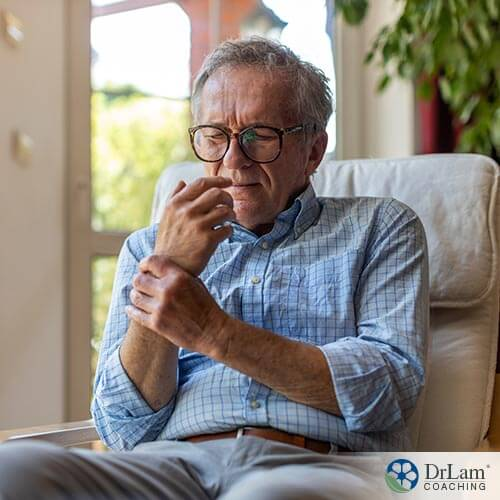 An image of an old man holding his wrist in pain
