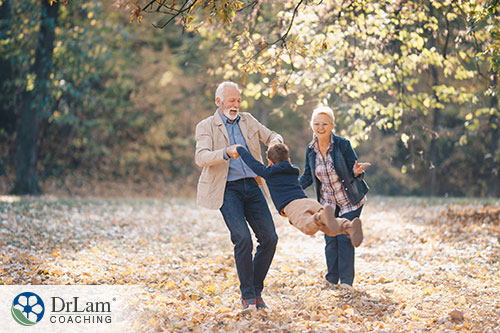 An image of an older couple and their grandson playing outdoors