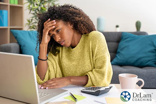 An image of a woman working on her laptop holding her head
