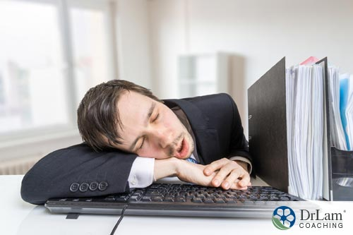 An image of a man asleep on his keybord in a suit, needing some sleep problem solutions for his fatigue and reduced productivity