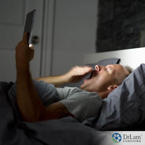 An image of an older man in bed with an electronic, which is one thing needing to be eliminated according to these sleep problem solutions