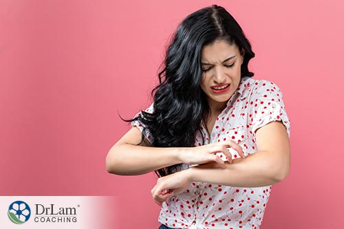An image of a woman scratching her arm because of a soy sauce allergy or gluten sensitivity