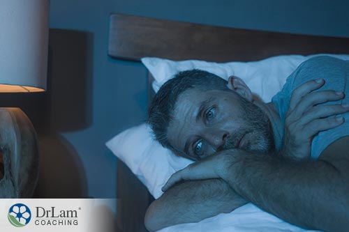 An image of a depressed man laying in bed unable to sleep