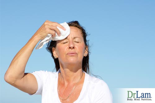 A woman in the sun wiping sweat off her brow and looking overheated, a possible sign of adrenal fatigue symptoms