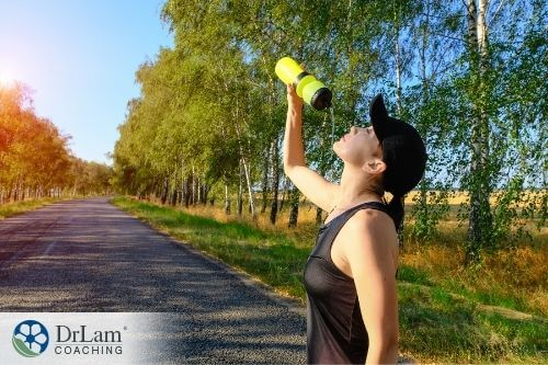 An image of a woman drinking water out of a sports bottle