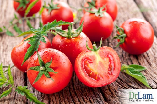 Several tomatoes, one of them cut in half, on a rough wooden surface like a wooden table. Acidic foods like tomatoes can neutralize digestive enzymes in the mouth, with consequences for what else you can eat in the food combining diet.