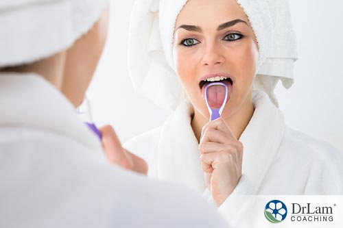 An image of a young woman scraping her tongue after a shower