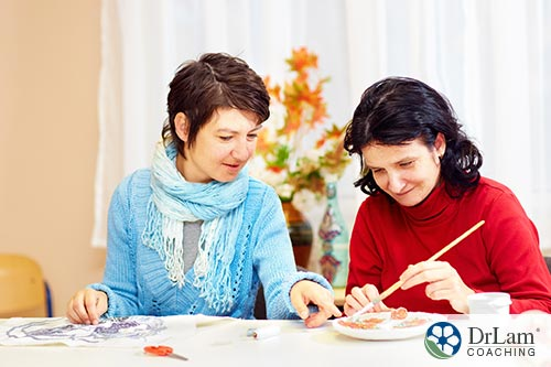 An image of a woman doing painting crafts with another woman who is autistic