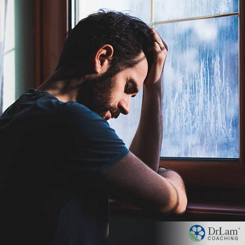 An image of a depressed man holding his head next to a window