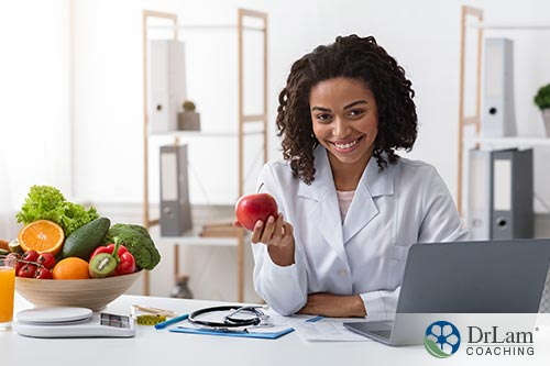 An image of a doctor smiling and holding an apple