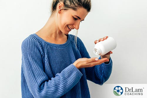 An image of a woman holding a bottle of vitamins