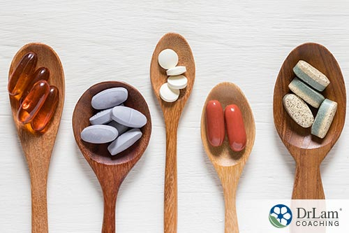 An image of five wooden spoons with different vitamins in them