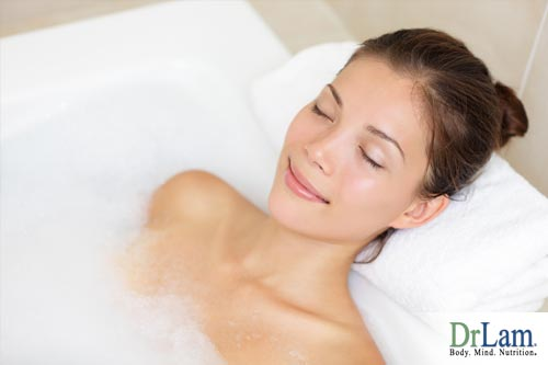 A young woman relaxing in a bath, another tactic along with the best temperature for sleeping that can help with rest.