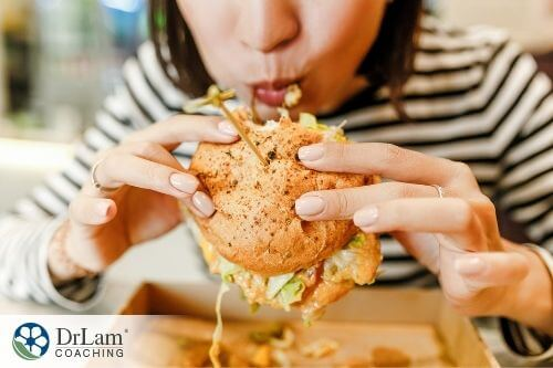 An image of a woman eating a burger